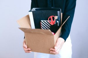 Une personne porte un carton avec ses affaires de bureau à l'intérieur.