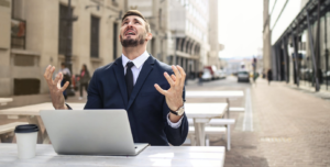 Un homme en costume assis à une terrasse face à son ordinateur portable. Il regarde le ciel avec un air désespéré et ses mains lui donnent l'air d'être frustré