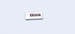 """Le mot """"Think"""" écrit sur un morceau de papier blanc sur un fond neutre bleu clair."""