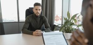 Un entretien d'embauche : deux hommes l'un en face de l'autre à une table. L'un des deux regarde un CV pendant que l'autre le regarde.