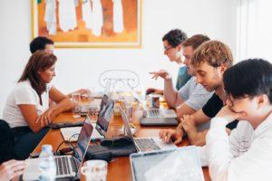 Une équipe de personnes assises autour d'une table avec leurs ordinateurs portables.