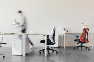 Une personne marche derrière des bureaux minimalistes. Elle est en flou.