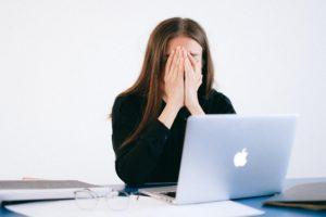 Une femme assise à une table devant un ordinateur portable ouvert. Elle se cache le visage avec les mains ; elle semble fatiguée ou stressée.