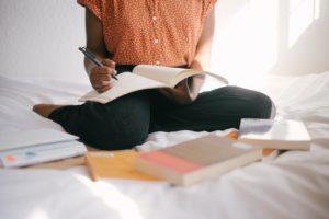 Une femme assise sur un lit avec plein de livres autour d'elle. Elle a un livre ouvert devant elle et elle tient un crayon.