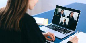 Une femme est en visio-conférence avec des collègues et prend des notes sur un papier.