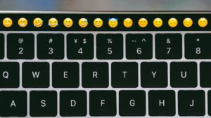 Un claivier de Macbook avec des emojis sur la touchbar.