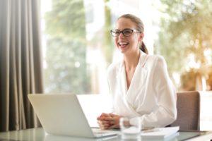 Une femme assise devant son ordinateur semble rire avec quelqu'un qui se trouve hors de la photo.