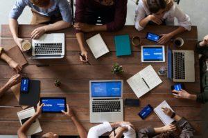 Une table vue d'en haut avec une équipe de personnes travaillant sur des ordinateurs portables.