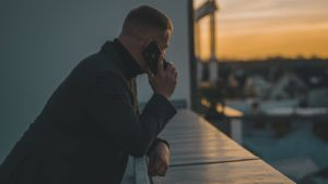 Un homme accoudé à un balcon passe un coup de téléphone en regardant à l'horizon.