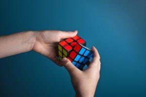 Des mains en train de résoudre un Rubik's Cube sur un fond bleu.