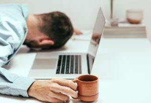 Un homme avec la tête posé sur une table à côté de son ordinateur. Il porte une tasse de café et a l'air de dormir.
