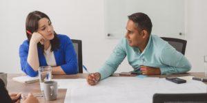 Un homme et une femme assis côte à côté à une table pendant une réunion de travail. La femme regrde l'homme, car il parle.