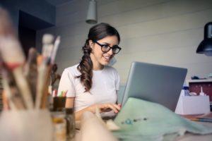 Une femme qui sourit devant un ordinateur. Il y a des pinceaux et de la peinture sur son bureau.