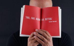 Un homme tient un livre rouge devant ses yeux avec une phrase inspirante sur l'échec.
