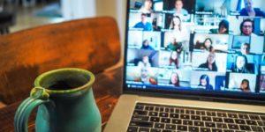 Un ordinateur ouvert sur une visio-conférence et un mug à côté.
