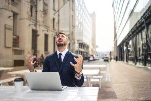 Un homme assis en terrasse avec son ordinateur. Il lève les bras au ciel et il a l'air désespéré.